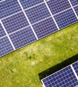 Third part of solar panels in green meadow