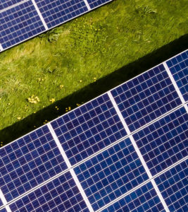Fourth part of solar panels in green meadow