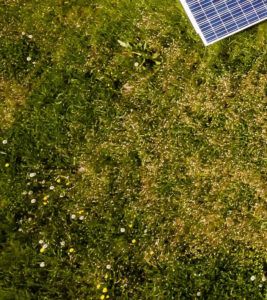 Fifth part of solar panels in green meadow