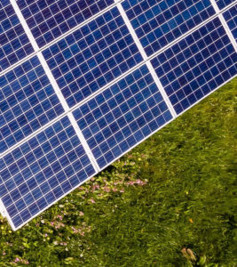 Eighth part of solar panels in green meadow